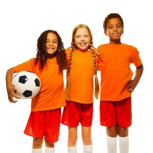 3 kids smiling in sports uniforms holding a soccer ball