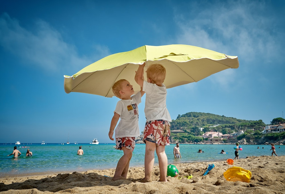 sunburn symptoms, treatment and risks - young boys under umbrella on beach