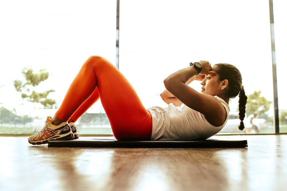 woman doing sit ups - healthy resolutions