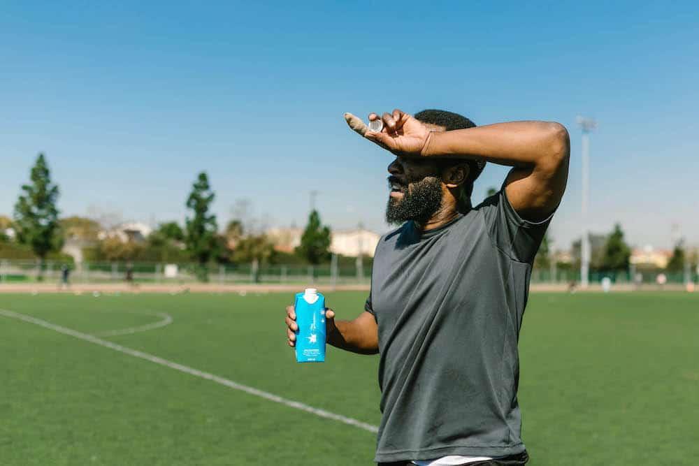 man standing on soccer field shielding eyes from sun drink water symptoms of heat-related illness