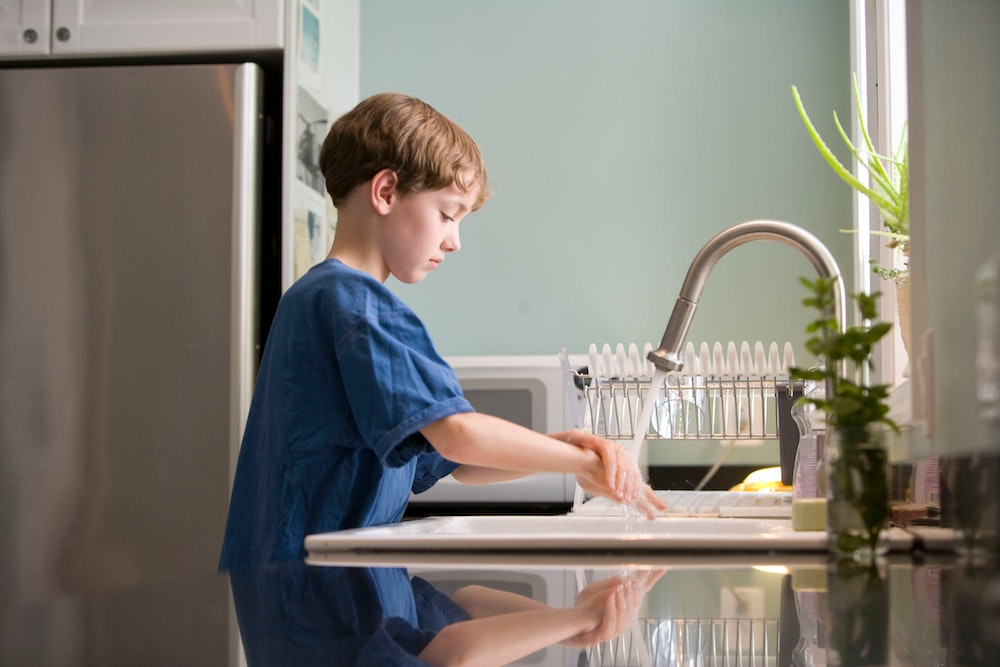 young boy washing hands to prevent respiratory illnesses